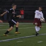 Wildcat Romel Giron #10, Whitman's senior captain and midfielder, works the ball around Sam Ducker of Newfield.